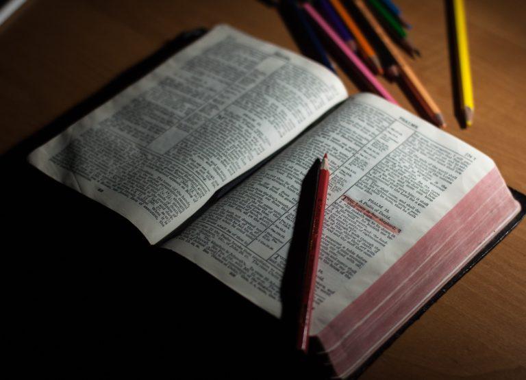 Otevřená bible s pastelkami